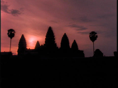 The sky glows orange behind Angkor Wat, Cambodia during... Stock Video Footage