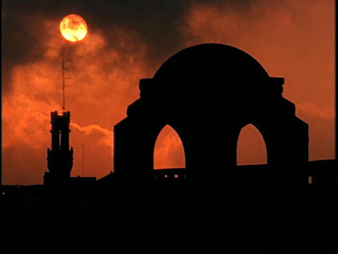 The sky glows orange behind a dome in Jerusalem during... Stock Video Footage
