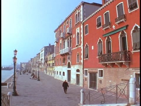 A pedestrian walks past a brightly colored building in Venice Footage