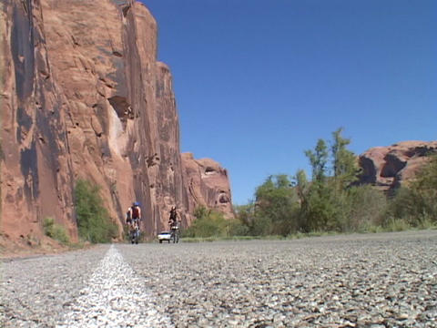 A cliff towers above bike racers Stock Video Footage