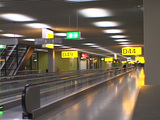 Signs glow above an empty airport terminal Footage