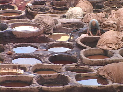 Workers dye leather in ancient pots Footage