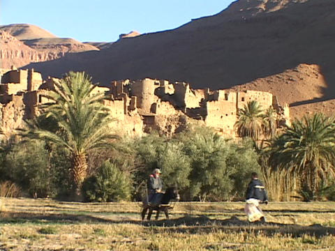 Moroccan men meet on the road in front of a deserted fortress in the Morocco desert Live Action