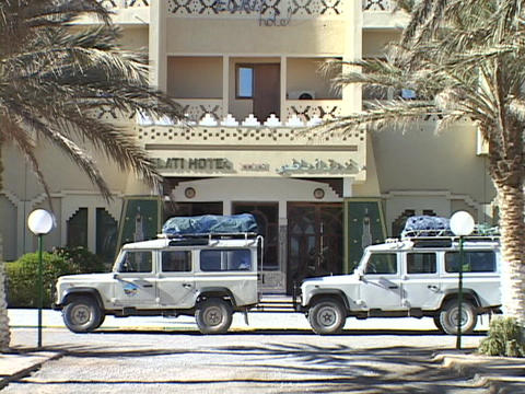 Land Rovers sit parked in front of a hotel prepared for a Safari Live Action
