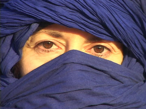 The eyes of an Arab woman show through her blue abaya Footage