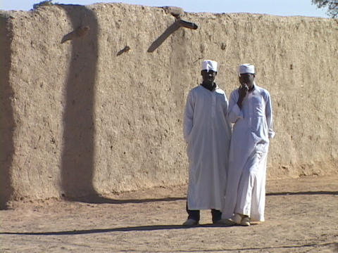 Sudanese men wear kaftans in front of a stone wall Stock Video Footage