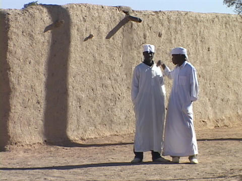 Sudanese men wear kaftans in front of a stone wall Footage