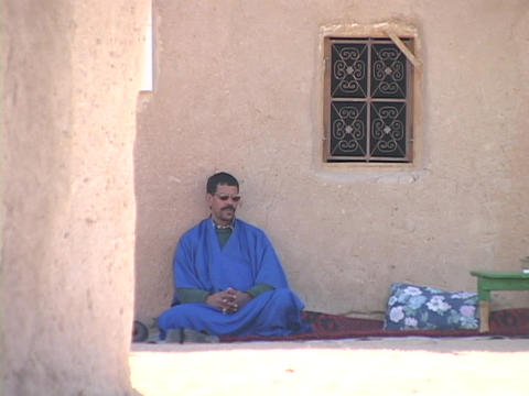 A man in a blue robe sits against a stone wall Stock Video Footage