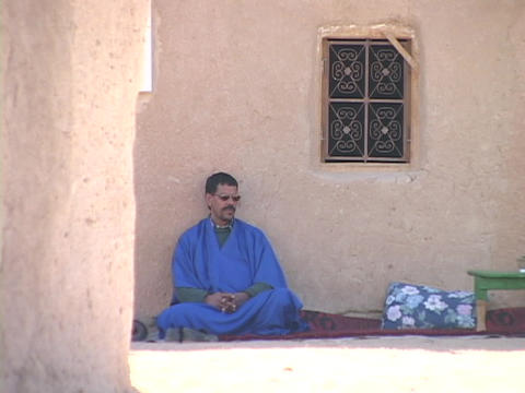 A man in a blue robe sits against a stone wall Footage