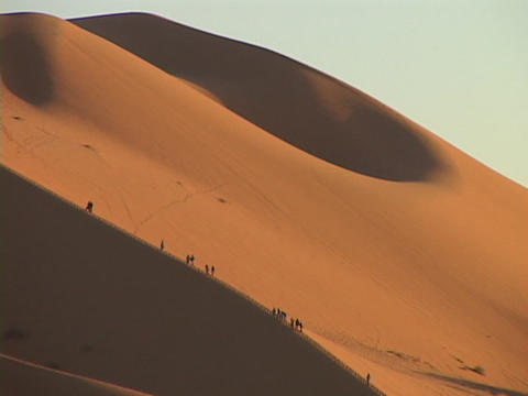 A caravan climbs up a large sand dune Stock Video Footage