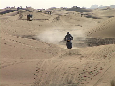 A motorcyclist rides across sand dunes Stock Video Footage