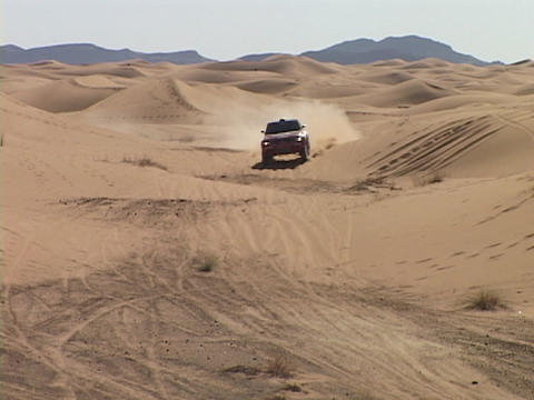 A rally car speeds through sand dunes as spectators watch Stock Video Footage