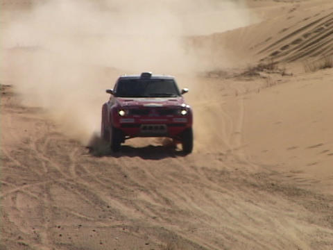 A rally car speeds through sand dunes as spectators watch Footage