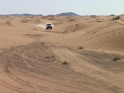 A rally car races across a desert course Footage