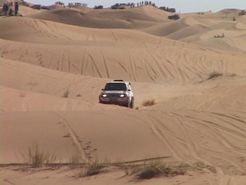 A rally car races across desert sand dunes Stock Video Footage