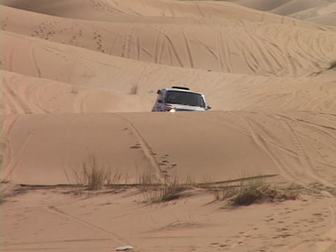 A rally car races across desert sand dunes Footage