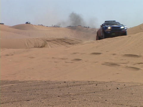 A race car races over hills in the desert Live Action