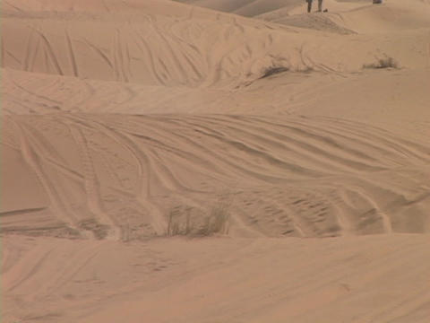A rally truck speeds around sand dunes on a desert course Stock Video Footage