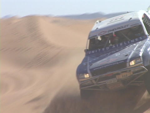 A rally truck speeds around sand dunes on a desert course Footage