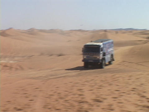 A rally truck races over the sand dunes Footage