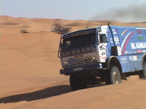 A rally truck races over the sand dunes Stock Video Footage