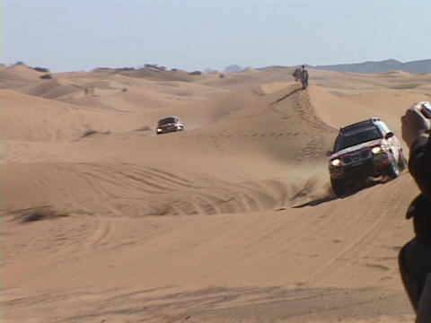 A race car races over hills in the desert Stock Video Footage