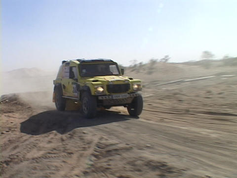A rally-car drives over a hill on a desert track Footage