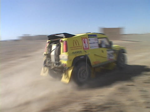 A rally-car drives over a hill on a desert track Stock Video Footage