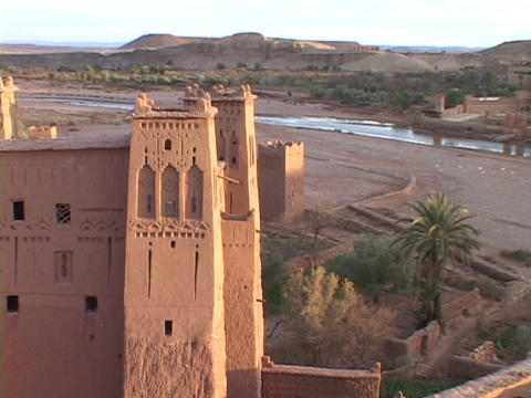 A building with decorative towers resides in a Morocco desert valley Footage