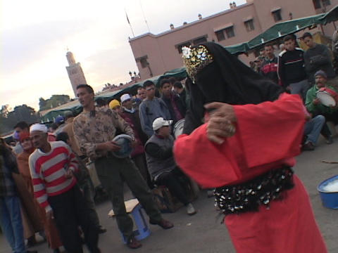 A person in traditional Islamic clothing dances for a crowd Footage