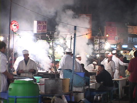 Steam rises as chefs cook outside on a busy city street Stock Video Footage