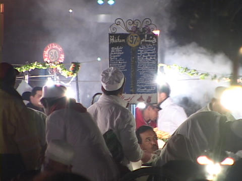 Chefs cook as customers walk around on a busy street Stock Video Footage