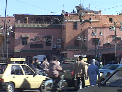Pedestrians and cars move along congested city streets in Marrakesh Morocco Live Action