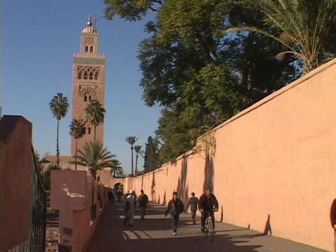 Pedestrians walk on a peaceful walkway away from a tall... Stock Video Footage