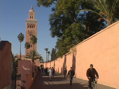 Pedestrians walk on a peaceful walkway away from a tall tower Live Action