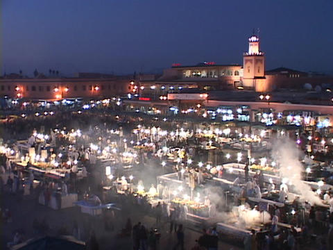 Smoke rises from food stalls at a night-time market in Marrakesh Morocco Footage