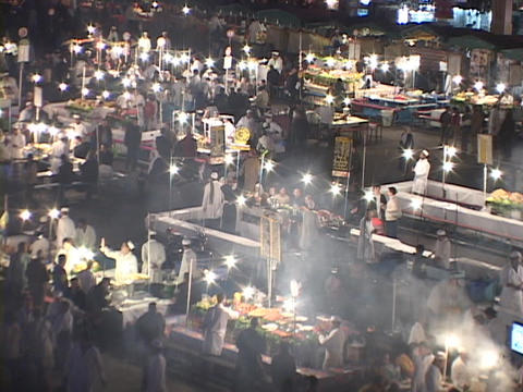 A busy outdoor cooking market comes to life at night in Marrakesh Morocco Footage