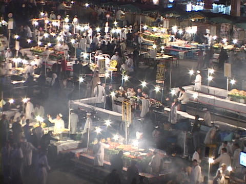 A busy outdoor cooking market comes to life at night in... Stock Video Footage