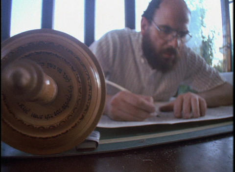 A Jewish scribe writes in a Torah scroll using a quill Stock Video Footage