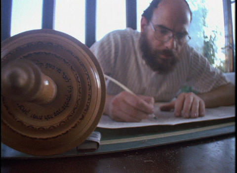 A Jewish scribe writes in a Torah scroll using a quill Footage