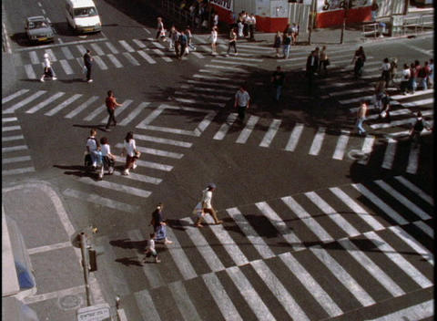 Pedestrians cross an intersection on crosswalks Stock Video Footage