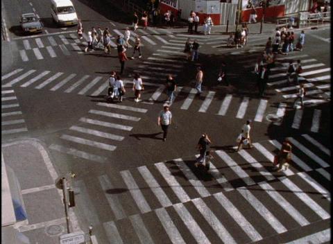 Pedestrians cross an intersection on crosswalks Stock Video Footage