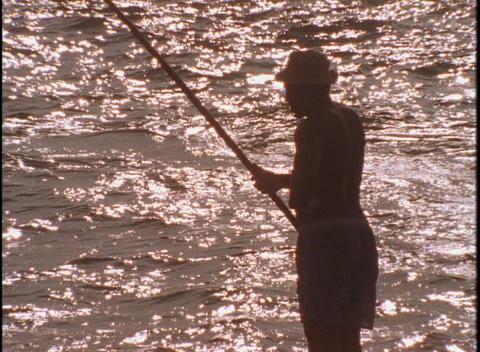 A fisherman checks his line Footage