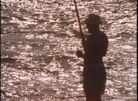 A fisherman checks his line Stock Video Footage