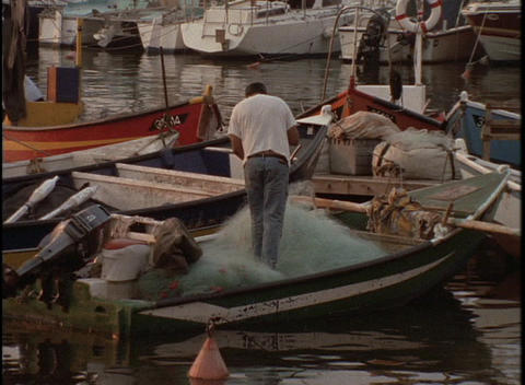 A fisherman works on his net on a small boat in a harbor Stock Video Footage