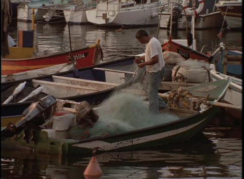 A fisherman works on his net on a small boat in a harbor Footage