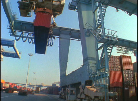 Cargo containers are lifted and moved by a huge crane in a port Footage