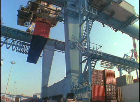 Cargo containers are lifted and moved by a huge crane in... Stock Video Footage