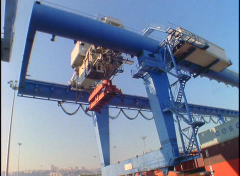 A truck passes under cargo held by a large crane Stock Video Footage