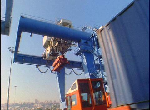 A truck passes under cargo held by a large crane Footage